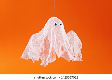 16 Diy Halloween ghost of starch and gauze on orange background. Gift idea, decor Halloween. Step by step. Top view. Process kid children Halloween craft. Workshop.