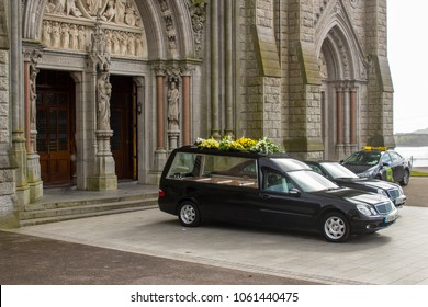16 March 2018 A hearse and a funeral car parked outside St Colman's Cathedral in Cobh Cork Ireland during a service for a local dignatory