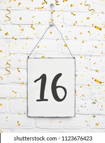 16 years old birthday party card text with golden confetti, number sixteen, metal plate white brick background