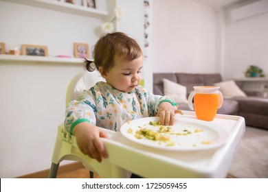16-month-old girl eating a plate of vegetables and eggs