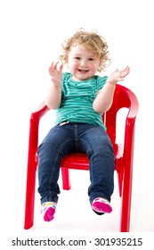 A 16-month-old toddler sitting clapping on a red chair, isolated against white background.
