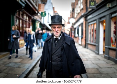 16th February 2018, The Shambles, York. Ghost Tour guide dressed as a menacing Victorian male undertaker in a top hat sneering at the camera in the UK
