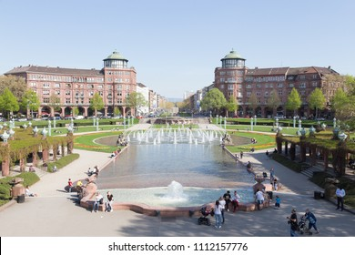 17 April 2018 / Mannheim,Germany:Fountain and Water Tower in spring with people sitting and relacing in the park, Mannheim.