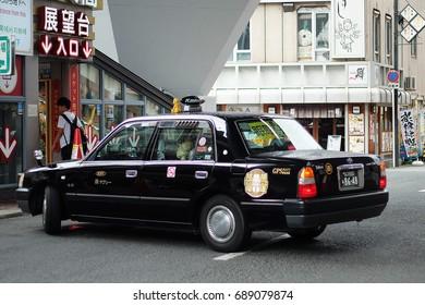 17 August 2016 - Taxi driver  U-turn a car around Tsutenkaku Tower in Shinsekai district, Osaka / Japan .