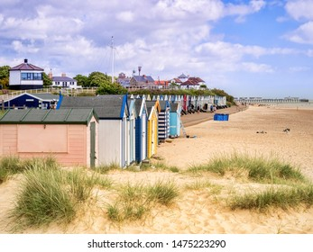 17 June 2019: Southwold, Suffolk, UK - The beach and beach huts, with the pier behind, at Southwold, Suffolk