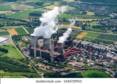 17 June 2019, Weisweiler, Germany. Aerial view of brown coal power plant close to Aachen. White smoke comes from three huge cooling towers. It is the most polluting factory in the country.