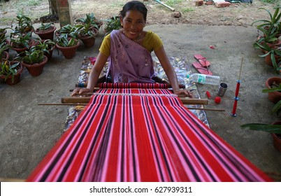 17 March 2017, Kaziranga, Assam, India. A Karbi Tribal Weaver smiling as she is busy in her work.