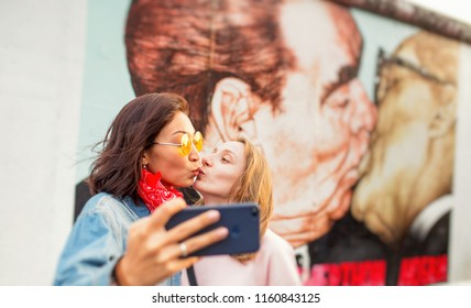 17 MAY 2018, BERLIN, GERMANY: Tourists takes photos with the famous kiss from the Berlin Wall