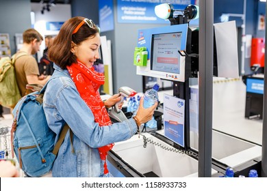 17 MAY 2018, DECATHLON, BERLIN, GERMANY: happy woman buying bottle of water at supermarket self-service cash register