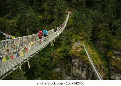 17 SEP 2019 ,Trekkers and Sherpa crossing a suspension bridge in Everest base camp route at (Sagarmatha National Park - Himalaya), Nepal.