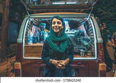 17/05/2019 Isfahan, Isfahan Province, Iran, young Iranian barista girl poses and smiles at a photographer leaning on a retro car