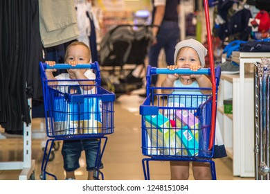 17/07/2018 Russia, Moscow. Two small caucasian of children the boy and the girl hold children's carts for goods on shopping in Children's shop. Around them a hanger with clothes