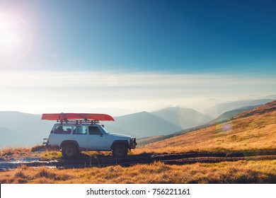 17.10.2017 Dragobrat, Ukraine. SUV car with kayak on the roof on a mountain trail. Vintage style shot with sunset and lens flare