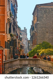 17.11.2016.Venice colorful corners,  old buildings and windows, people, water canal with reflections, boats and small bridge , Italy