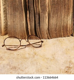 17th century book with vintage glasses, on grunge paper background