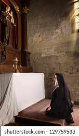 17th century church interior and a nun in prayer at the altar