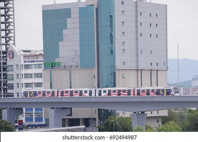 17th July 2017 : KUALA LUMPUR,MALAYSIA. Mass Rapid Transit (MRT) on the move with Malaysia Flag with building background.