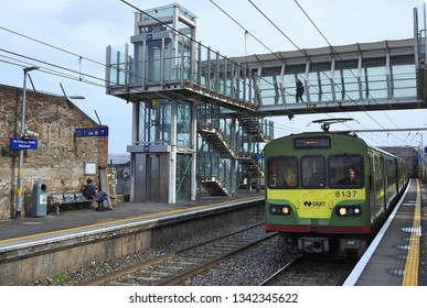17th March, 2019, Dublin, Ireland. Blackrock Dart Station with train approaching under overhead walkway.