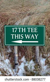 the 17th tee this way sign on an irish golf course in the winters snow