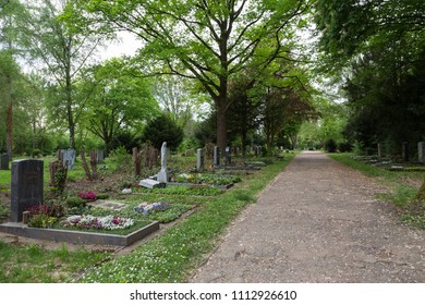 18 April 2018 / Frankfurt,Germany: Tombstone, memorials and headstones in the graveyard with great nature, green grass and flowers in cemetery-graveyard, Frankfurt Hauptfriedhof.