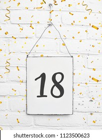 18 eighteen years old birthday party card text with golden confetti metal plate white brick background