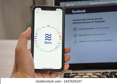 18 June 2019, Ljubljana Slovenia - Hand holding a smartphone with Libra logo on it and Libra's partners, next to Facebook website opened on laptop