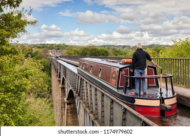 18 May 2016: Llangollen, Denbighshire, Wales, UK - Man at tiller, steering narrowboat over the Pontcysyllte Aqueduct, built by Thomas Telford, on the Llangollen branch of the Shropshire Union Canal.