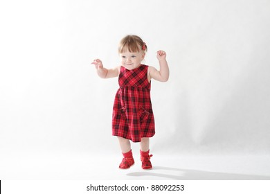 18 month old baby girl in red checked dress on white background