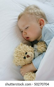 18 months old baby boy slepping in bed with sweet teddy bear. Little baby dreamer.