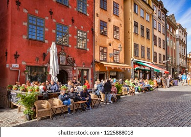 18 September 2018: Stockholm, Sweden - Tourists enjoying the sunshine outside the cafes and restaurants of Stortorget, the oldest square in the old town, Gamla Stan.