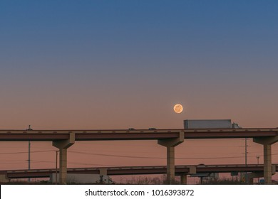 18 wheeler on highway overpass and moon at dusk