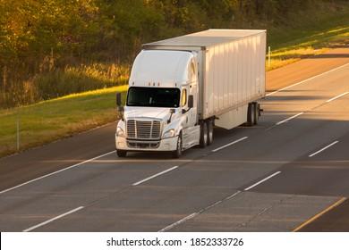 18 wheeler semi truck driving down the road.