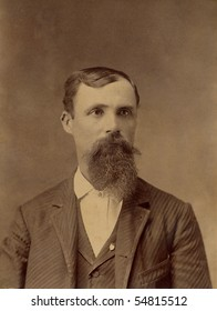 1800s Antique portrait of a man wearing a suit with a long beard. The photo is yellowed with age
