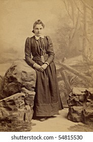 1800s Vintage portrait of a young girl. The photograph is yellowed with age. The young woman is dressed in the clothing of a Quaker religion.