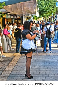 18.08.2017.Lifestyle fashion portrait of stylish young cosplay foreing woman in cosplay costume and hat waiting on street in Tokyo, Harajuku district, Japan