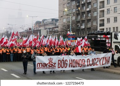 18/11/11 Warsaw Poland:  People walking with flags and the banner God Honour Fatherland in the street on the Independence Day.100 Years of Poland Regaining Independence.