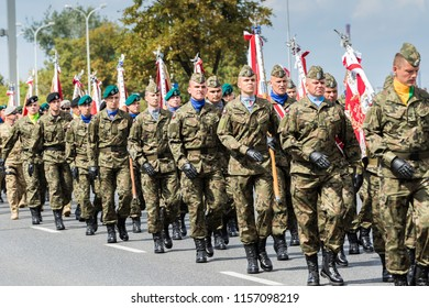 18/8/15 Warsaw Poland: Celebrating 100 Years of Poland Regaining Independence. Soldiers in green berets and forage caps with flag marching on  during the military parade on the Armed Forces Day