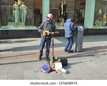 18th April 2019, Dublin, Ireland. Street performer playing a miniature guitar in Grafton Street,  Dublin city centre.