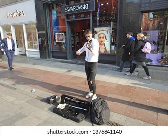 18th April 2019, Dublin, Ireland. Street performer playing a violin in Grafton Street,  Dublin city centre.