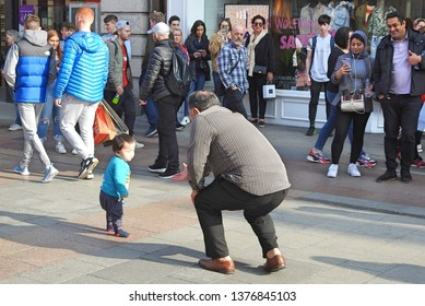 18th April 2019, Dublin, Ireland. Street performer singing opera on Grafton Street,  Dublin city centre,  reached out to dancing child.