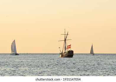 18th century sailing yacht and modern sailboats in an open sea at sunset. Holland. Old tall ship. Recreation, vacations, cruise, historical reenactment, past, history, regatta, transportation