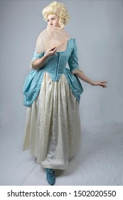 18th Century woman in blue bodice and cream skirt