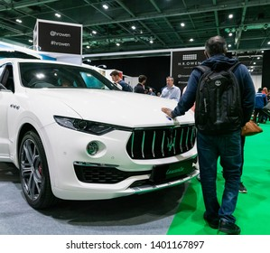 18th May 2019. London, UK. A man holds his hand on luxury Maserati Levante SUV at London Motor Show 2019.