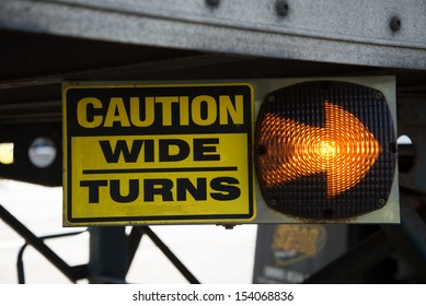 18-Wheeler Caution Wide Turns Sign with Lighted Arrow.  Sign is on the undercarriage of a trailer on a big rig truck.