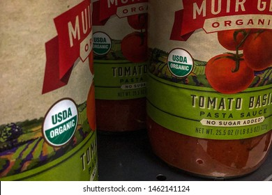 O'fallon, IL—July 19, 2019; illustrative editorial of green and white USDA Organic certification logos on the side of glass jars of pasta sauce on the shelf of a retailer.