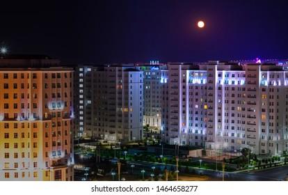 19 July 2019; Ashgabat, Turkmenistan; Full moon shining in a white city