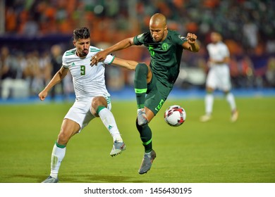 19 July 2019, Egypt, Cairo: Baghdad Bounedjah of Algeria battle for the ball with Senegal's player during the 2019 Africa Cup of Nations final match Senegal vs Algeria on Cairo International stadium