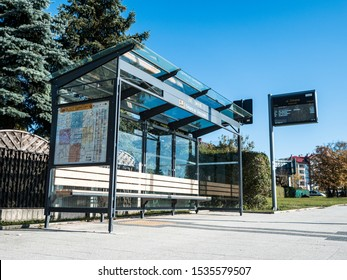 19 Oct 2019, Kielce, Poland, A bus stop on city street. In the background buildings and road. Poster and maps, bus time schedule information on street next to roadway in autumn day.