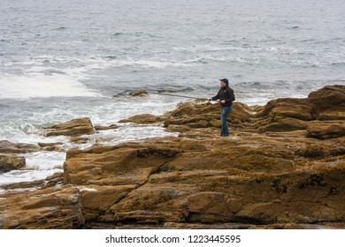 19 September 2014 A man fishing alone on the slippery rocks on the shore of Carlingford Lough near Newcastle County down in Northern Ireland. Probably jigging for mackerel.