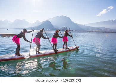 19.01.2019 - France Lake Annecy GlaGla Race 2019. SUP paddlers girl team is participating in race in France Alps lake Annecy. Cool pink dress. Fun in water board sport